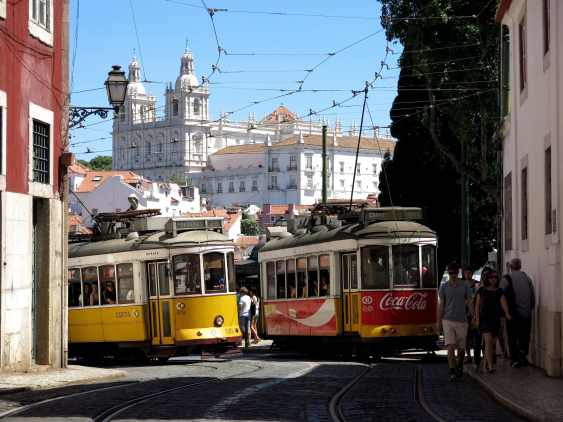 Lisbon's typical tram 28 direction prazeres with a red tram and a blue sky