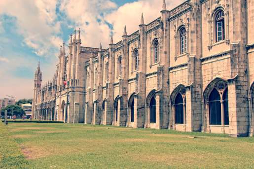 Mosteiro do Jeronimo in Belem Lisbon Portugal with green grass and clouds in a blue sky