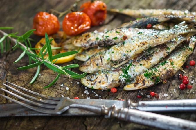 grilled sardines with tomatoes and herbs next to a fork and a knife served in our gourmet food tours in Lisbon at Treasures of Lisboa