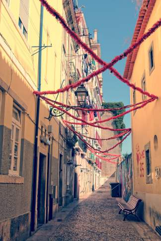 Narrow street in Lisbon with colorful decorations and sunlight