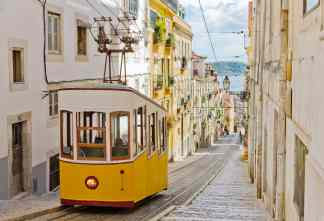 Elevador de santa justa in Lisbon yellow tram blue sky and houses with flowers