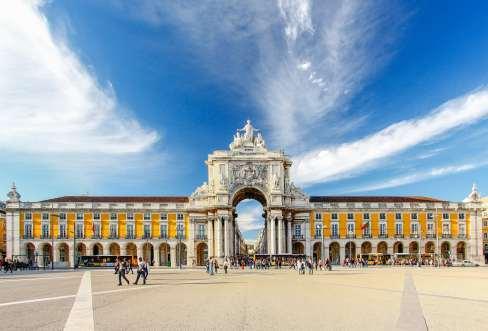 Praça do comercio in Lisbon with a blue sky and tourists walking around