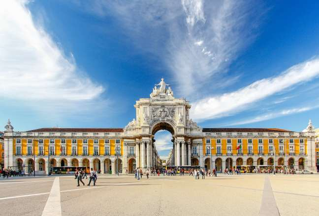 Praça do comercio in Lisbon with a blue sky and tourists walking around