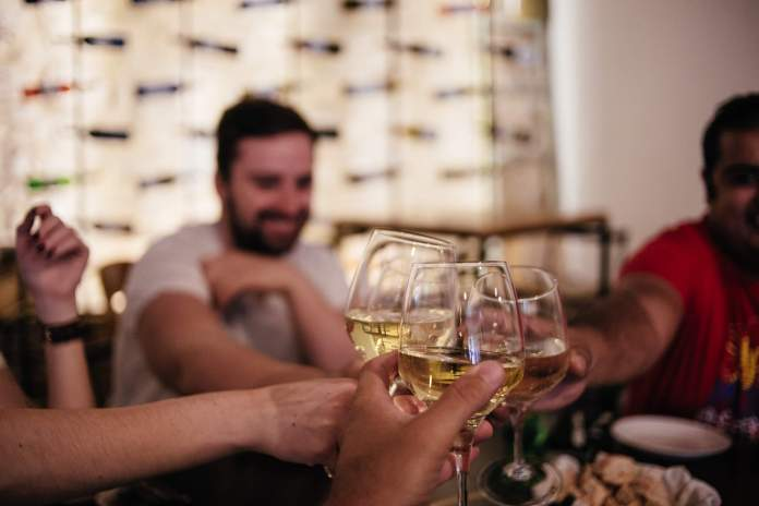 People cheering with green wine to be tasted during the best food tour in Lisbon with treasures of lisboa food tours