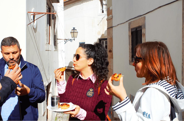 treasures of lisboa food tours in lisbon - group eating pastel de nata