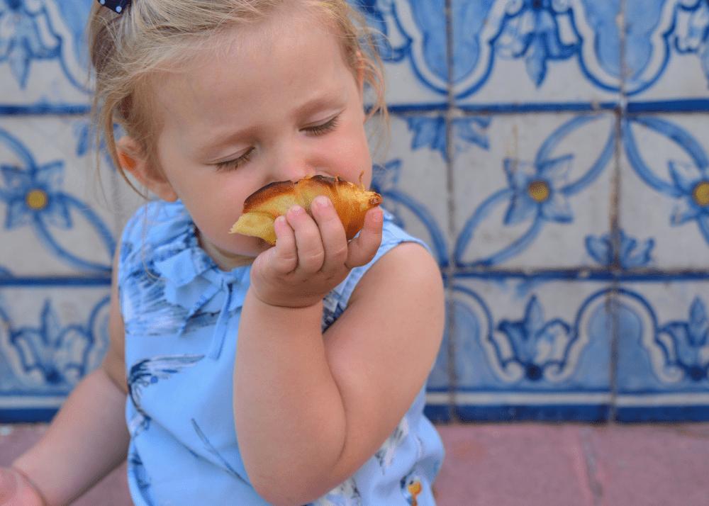 child eating pastel de nata in lisbon by treasures of lisboa food tours